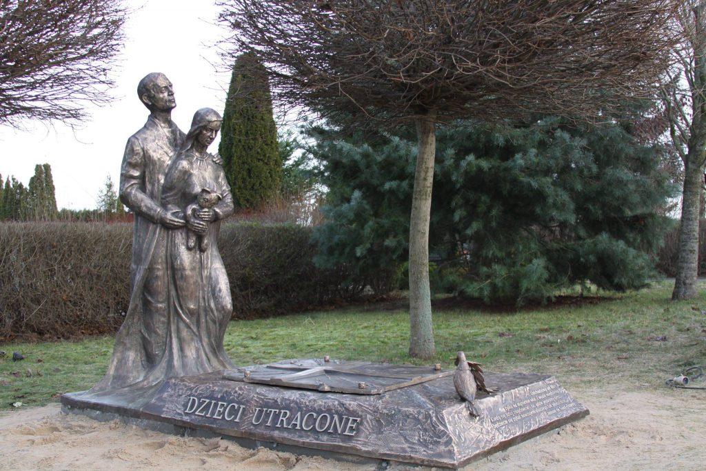 rzeźba mężczyzny obejmującego kobietę trzymającą pluszowego misia