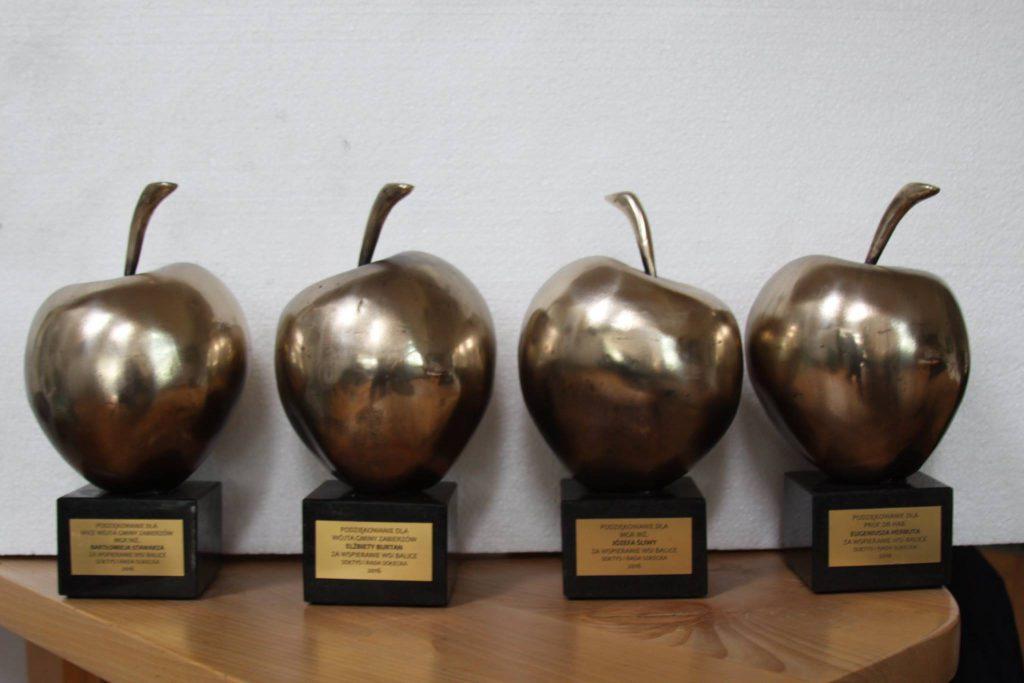 cztery statuetki mosiężnych jabłek na drewnianych podstawach
